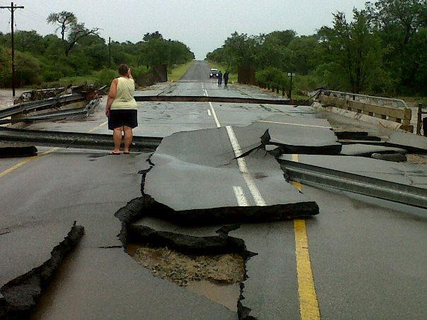 A woman looks on at roads absolutley destroyed by floods