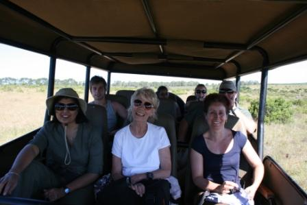 volunteers at the Shamwari Conservation experience sit on the jeep, scouting out wild animals