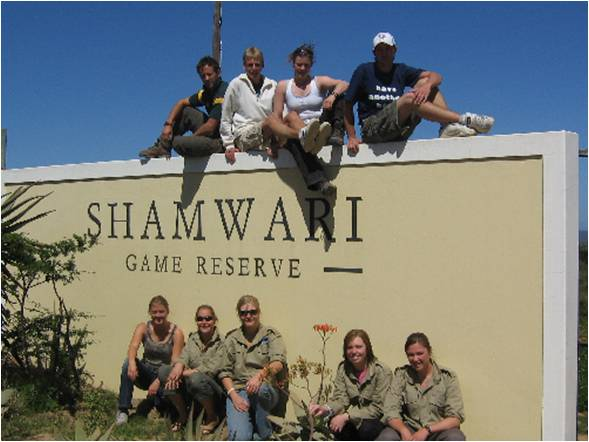 volunteers and staff take a break on the Shamwari Game Reserve sign