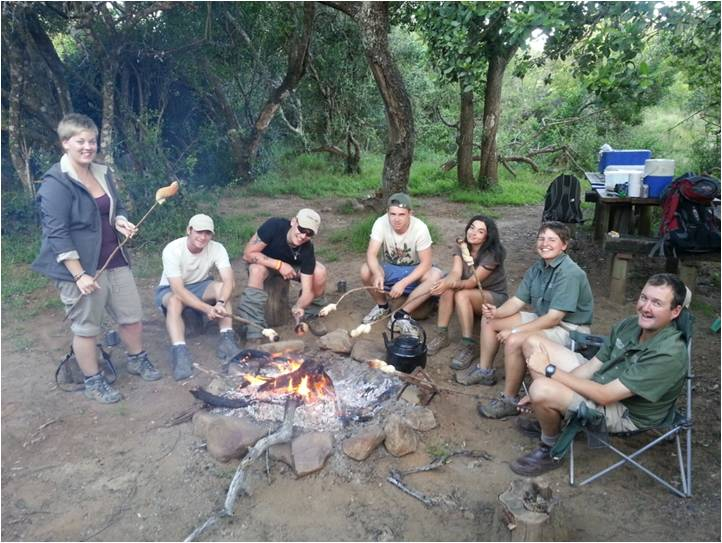 volunteers and the Shamwari team share food around a campfire