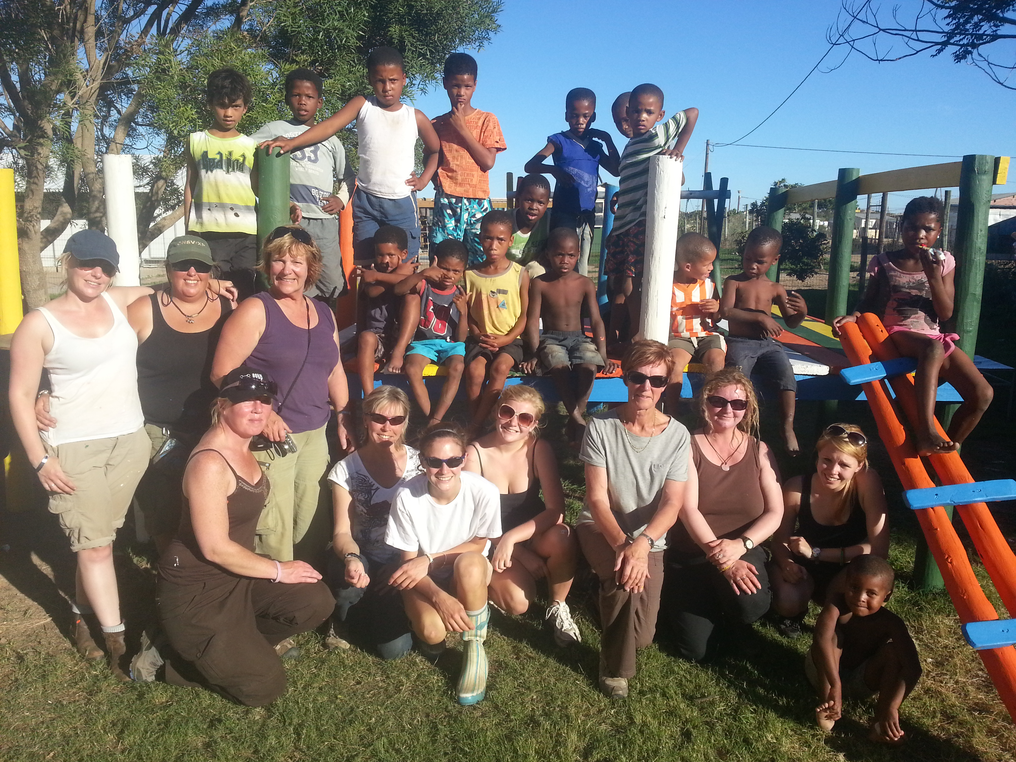 volunteers pose with members of the local community after building a jungle gym