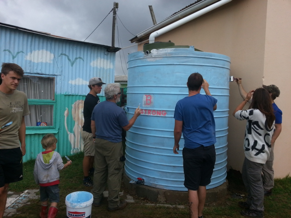 Volunteers use their creativity to paint a water tank in the local community