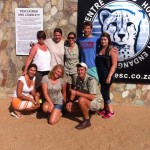 A group of volunteers by the Hoedspruit endangered species centre sign