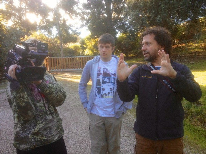 Volunteer instructed on how to use a video camera by an instructor