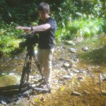 A volunteer using a video camera on a stream in africa