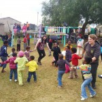Volunteers dancing with school kids