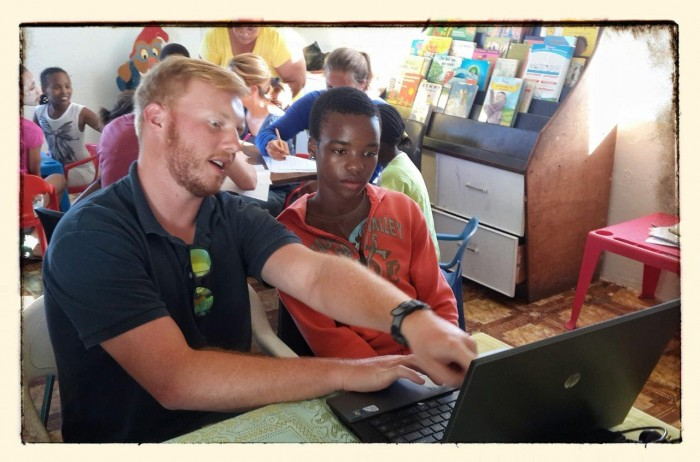 A volunteer shows a local boy how to use a laptop