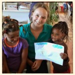 A young girl shows off a picture she drew with a volunteer