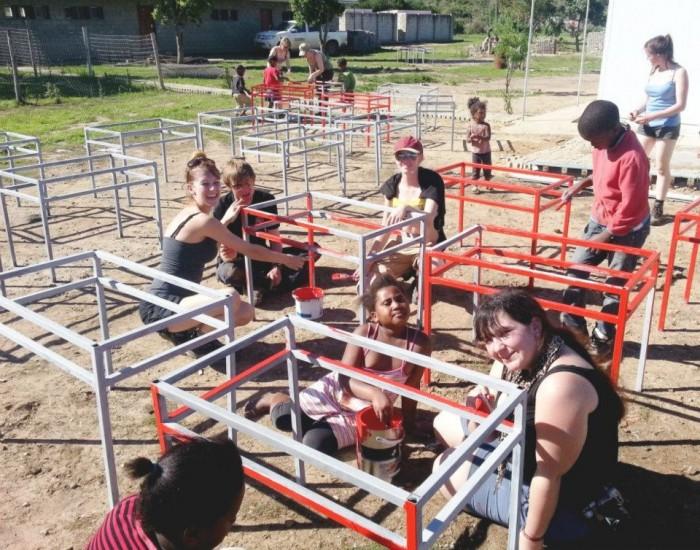 Volunteers painting desks with children