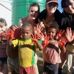 Volunteers and children show off their painting hands