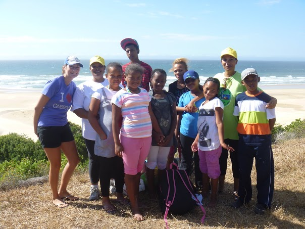 A volunteer and school children down at the beach