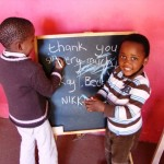 Local children drawing on a chalk board