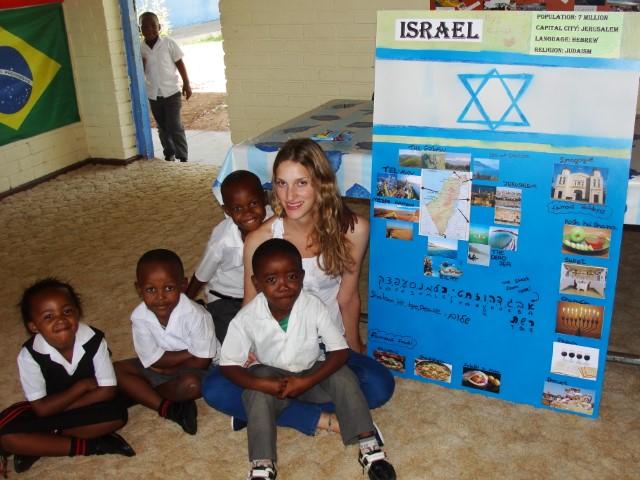 A volunteer sitting with school children
