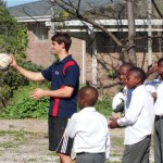 A volunteer playing football with children