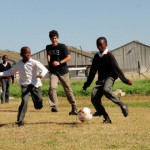 A volunteer playing football with local children