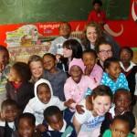 Volunteers pose with school children
