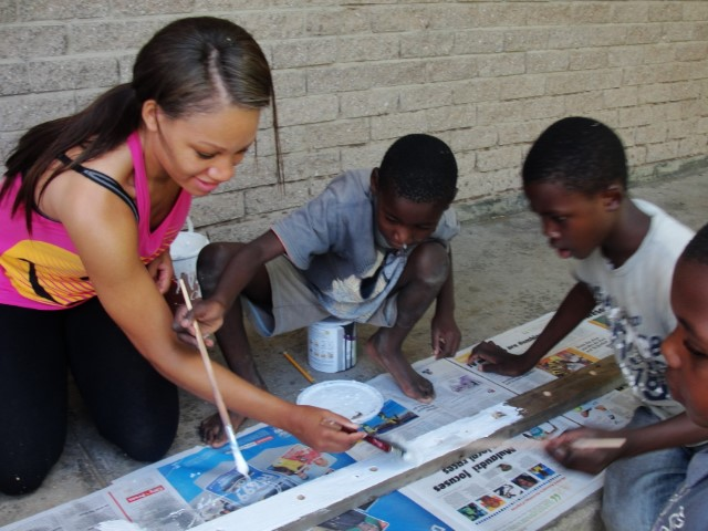 A volunteer paints wood with local children