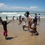 Volunteers play in the sea with local school children