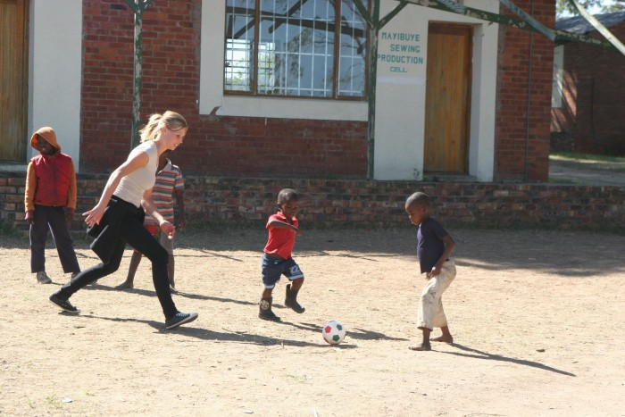 A volunteer kicking a ball with local school children