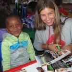 Volunteers cutting up magazines with school children
