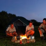 Game rangers gather round a campfire