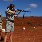 A volunteer practices her shooting as a game ranger watches on