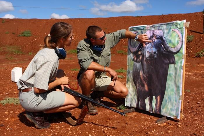 A Shamwari game ranger shows a volunteer her shots on the buffalo board