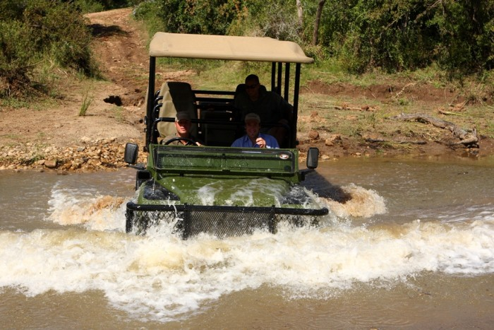 Game rangers travel across a stream in the jeep with volunteers