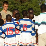 Local football players discuss tactics as a volunteer watches on