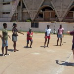 A volunteer teaching members of the local community how to play netball