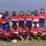 Rugby coaching volunteers pose in a team picture with members of the community