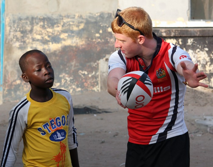 A volunteer instructs a young boy how to pass a rugby ball
