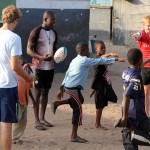 A rugby coach shows the african kids how to stretch their quadricep.