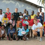 A group picture of volunteers and students learning rugby