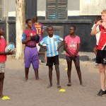 Young children listen as their rugby coach gives out instructions
