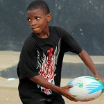 A young boy holding a rugby ball