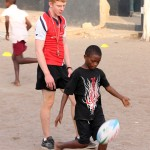 A child kicks a rugby ball as his coach watches on