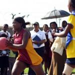 A school girl plays netball as her peers watch on