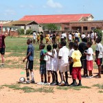 A volunteer training kids on how to pass a football