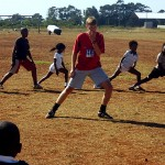 A volunteer shows some of the local youths how to stretch