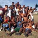 A volunteer poses with a group of local footballers