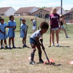 A volunteer watches on as a young girl hits a hockey ball