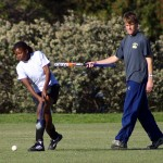 A volunteer helps an African girl with her striking technique in hockey