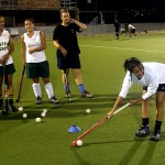 Teenage girls practice hitting their hockey balls