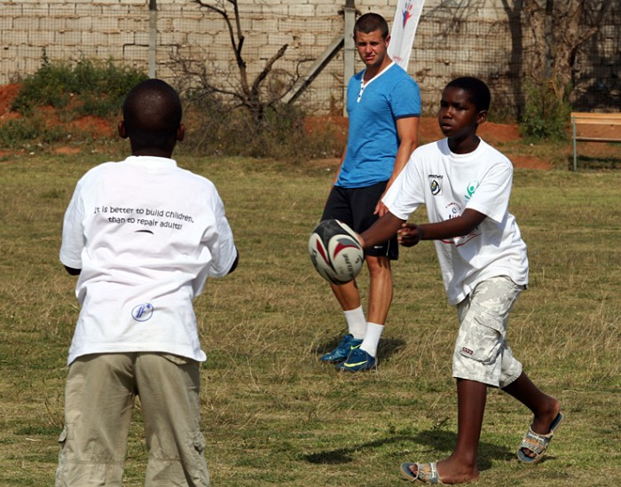 Two young boys play rugby as a volunteer coach watches on